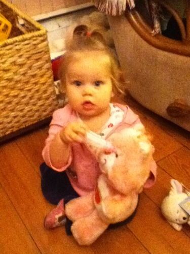 Keira feeding a bottle to her bear